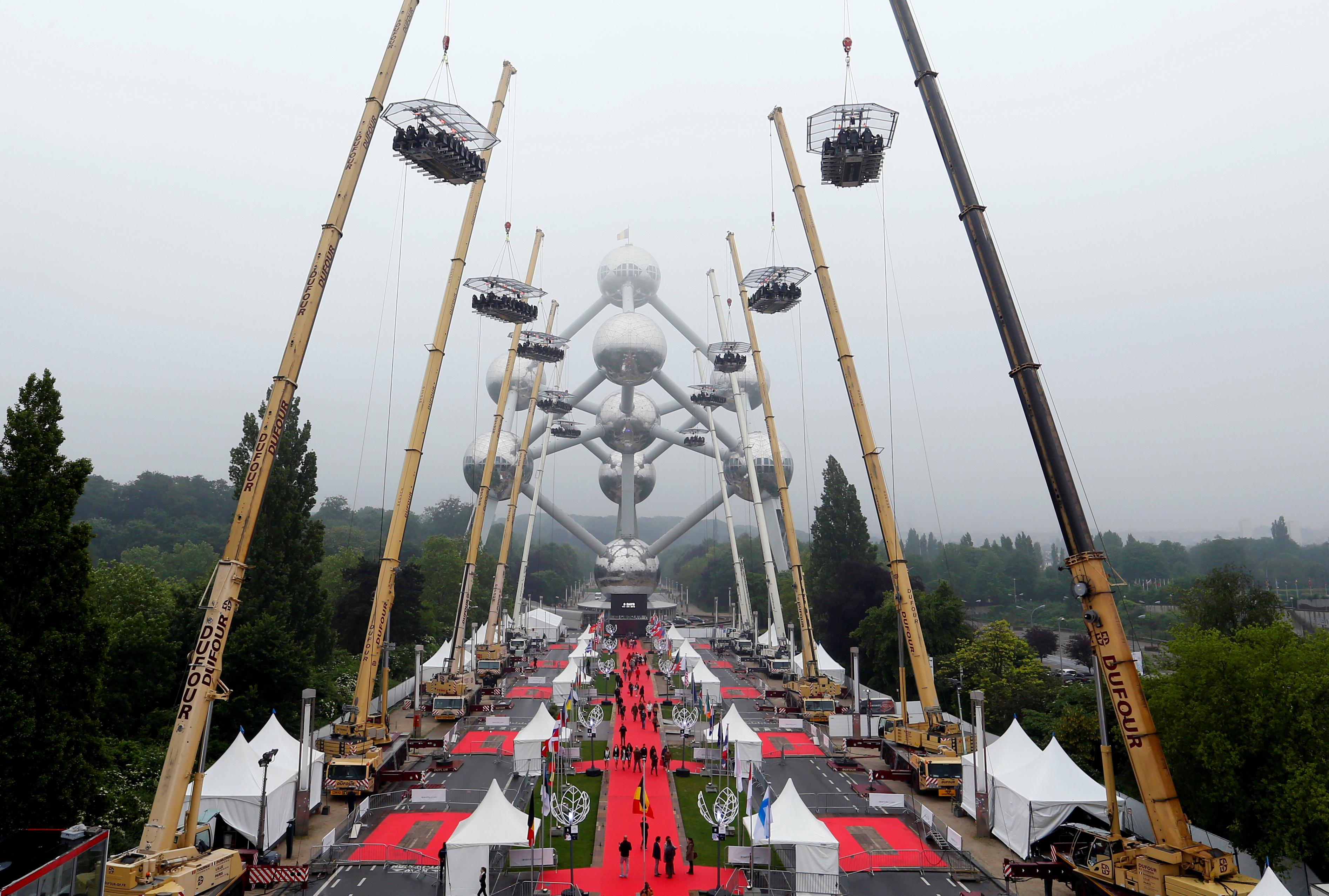BRUSSEL, BELGIA: Ti bord med tilsammen 220 middagsgjester ble løftet 40 meter over bakken av heisekraner for å markere 10-årsjubileet for en begivenhet kalt «Dinner in the Sky». FOTO: Yves Herman / NTB scanpix