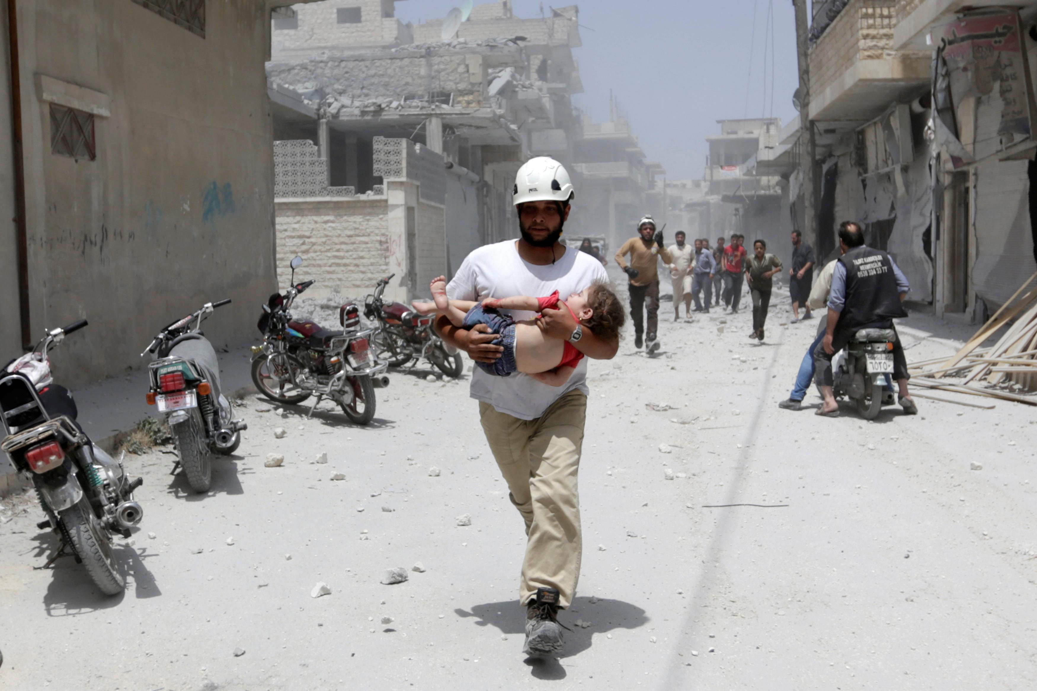 MAARET AL-NUMAN, SYRIA: En mann fra sivilforsvaret bærer en skadet jente vekk etter bombeangrep i den opprører-kontrollerte byen Maaret al-Numan i Idlib-provinsen i Syria. FOTO: Khalil Ashawi / NTB scanpix