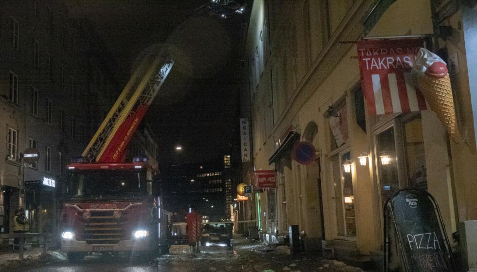 Mannskaper fra Oslo brann- og redningsetat fjerner is fra taket på et bygg i Dronningens gate i Oslo sentrum sent lørdag kveld, etter at en mann tidligere på kvelden ble fraktet til legevakt etter å ha fått en isklump i hodet da han passerte stedet. Foto: Paul Kleiven / NTB scanpix