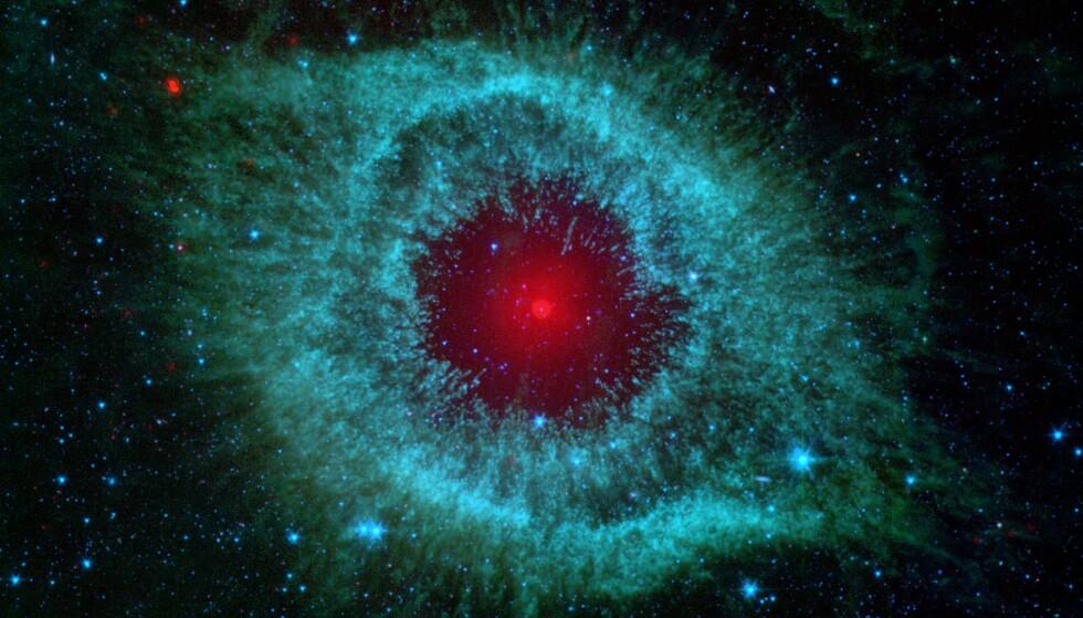 Gasskyen Helix Nebula viser hvordan vårt solsystem trolig ser ut om fem milliarder år, etter at Solen har ekspandert og slukt det indre solsystemet, før den kvitter seg med mesteparten av sin egen masse og blir en liten, glødende hvit dverg. Helix Nebula ligger i vår galakse Melkeveien, cirka 700 lysår fra Jorden. Foto: NASA/JPL-Caltech/Univ. of Arizona / SCANPIX