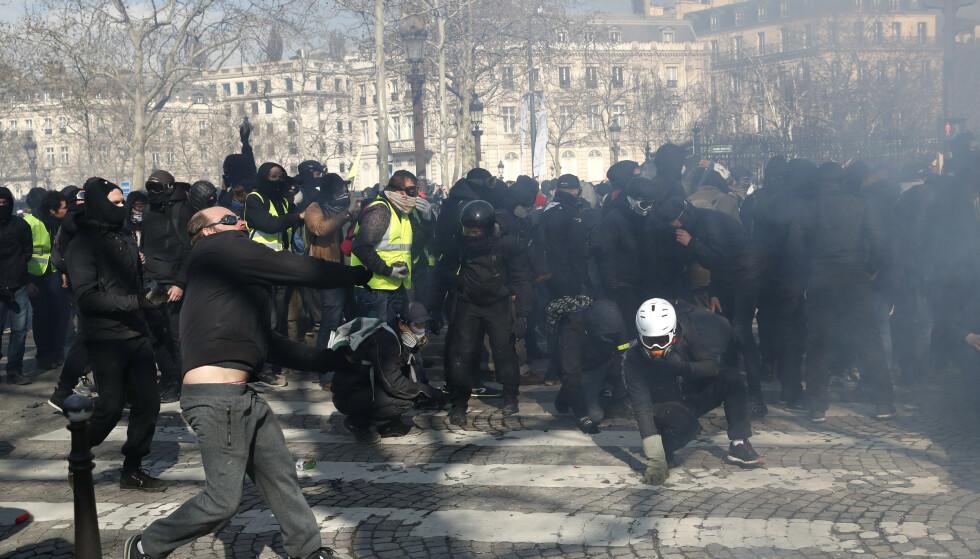 Det gikk voldsomt for seg da demonstranter støtte sammen med opprørspoliti i Paris lørdag. Foto: AP / NTB scanpix