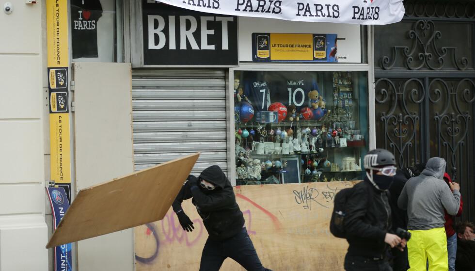 Maskerte demonstranter vandaliserer en butikk nær Triumfbuen i Paris. Foto: AP / NTB scanpix