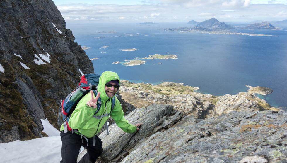 Nordmenn er nummer tre på lista over de lykkeligste i verden. Denne mannen er på tur opp på Tomskjevelen på Helgelandskysten. Bak i bildet Lurøya, Stigen og Hestmona. Foto: Gorm Kallestad / NTB scanpix