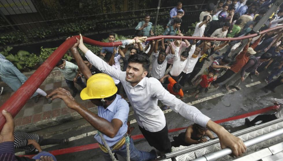 Lokale innbyggere hjelper brannfolkene ved det brennende høyhuset i Dhaka. Foto: Mahmud Hossain Opu / AP / NTB scanpix