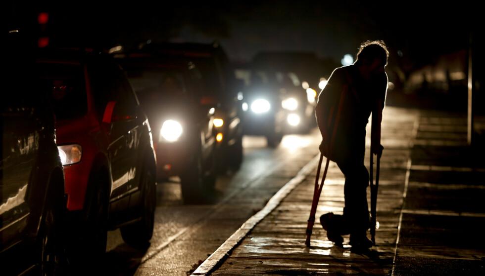 I helgen har det vært en rekke strømbrudd i Venezuela. Her går en mann gatelangs i den mørklagte hovedstaden Caracas fredag, hvor de eneste lysene som finnes kommer fra bilene. Foto: AP / NTB scanpix
