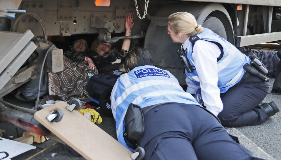 Politiet snakker med demonstranter som har lagt seg under en lastebil for å blokkere Waterloo Bridge i London. Foto: AP Photo/Frank Augstein / NTB scanpix