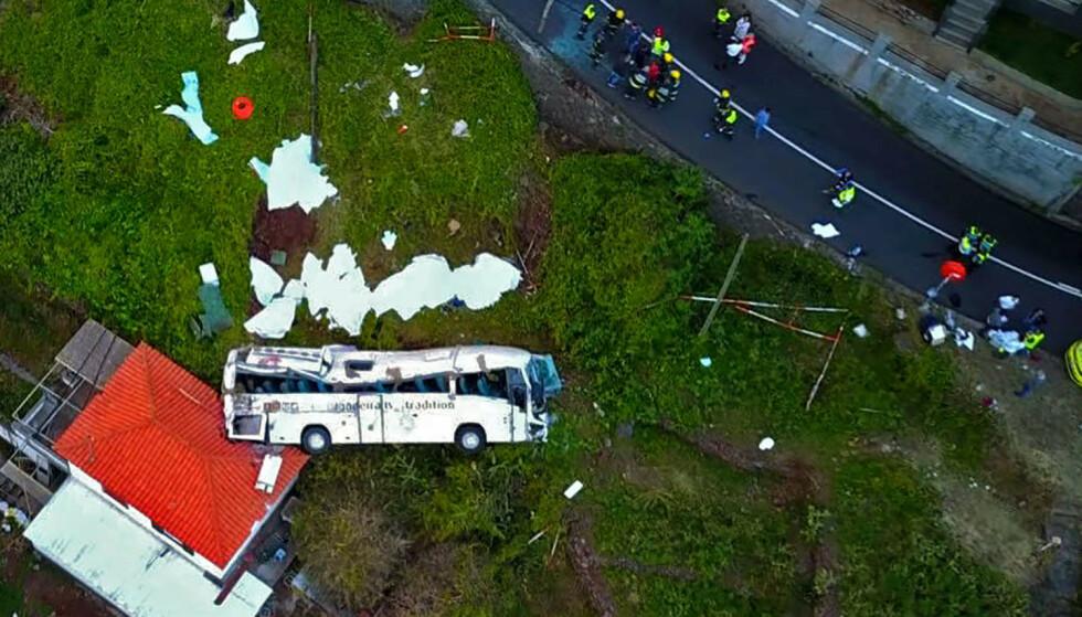 Bussen landet på taket til et hus under skråningen. Portugisiske myndigheter opplyser at de har startet etterforskning av ulykken. (FOTO: AFP).