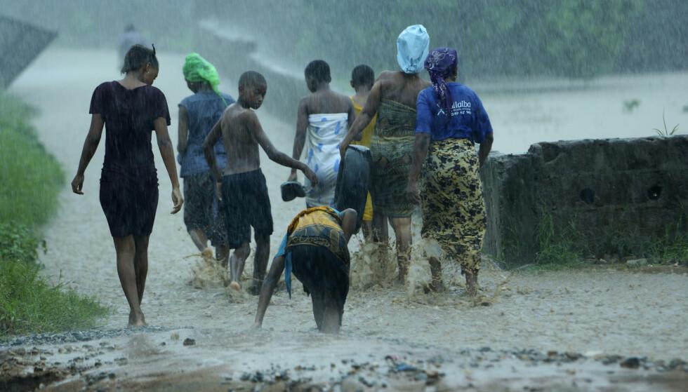 Innbyggere i Pemba forlater en flomrammet bolig i bydelen Natite mens regnet høljer ned søndag. Foto: Tsvangirayi Mukwazhi / AP / NTB scanpix