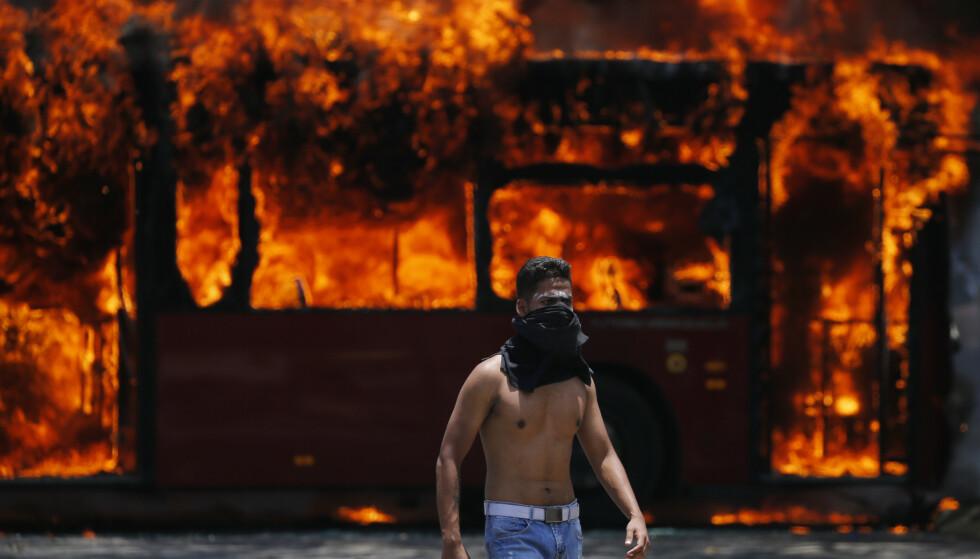 En opposisjonell demonstrant går forbi en buss som ble satt i brann av motstandere av president Nicolás Maduro. Foto: AP / NTB scanpix