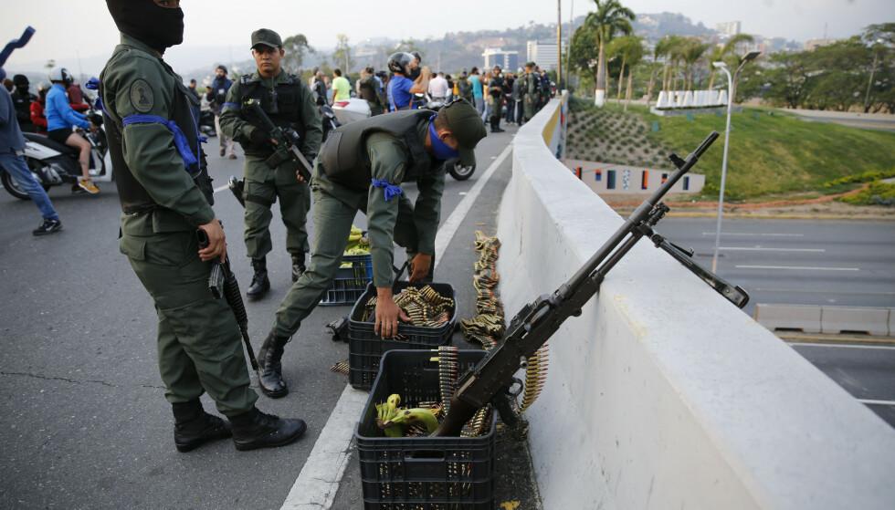 Soldater inntar stillinger på ei motorveibru nær flybasen La Carlota. Foto: AP / NTB scanpix