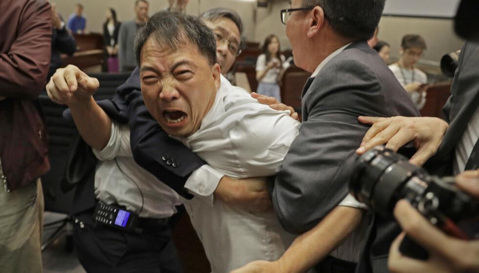 En av opposisjonens representanter, Wu Chi-wai, forsøker å komme seg unna sikkerhetsvakter under bråket i Hongkongs folkevalgte forsamling. Foto: Vincent Yu / AP / NTB scanpix