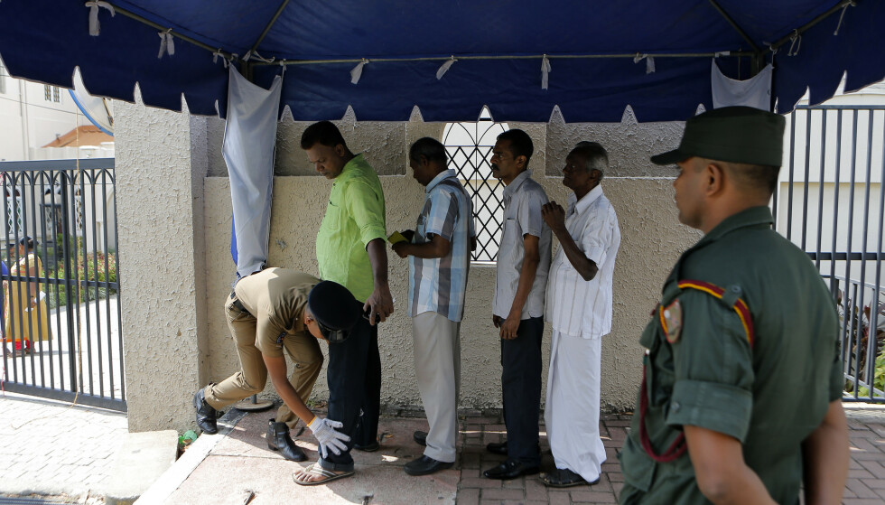 En soldat kroppsvisiterer troende som er på vei inn til gudstjeneste i en katolsk kirke i Colombo søndag. Mandag blokkerte myndighetene i landet flere sosiale medier etter uro mellom ulike religiøse grupper. Foto: AP / NTB scanpix