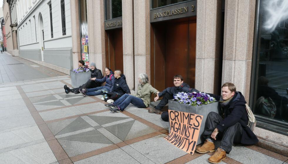 Demonstrantene på utsiden av Norges Bank limte seg fast i hverandre. Foto: Terje Bendiksby / NTB scanpix