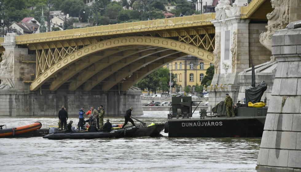 Redningsarbeidere forbereder seg på å heve den over 70 år gamle båten opp fra Donau. Foto: AP / NTB scanpix