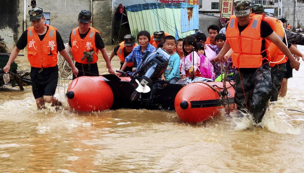 Kinesisk redningsmannskaper evakuerer beboere som har vært avskåret fra å komme seg i sikkerhet på grunn av vannmassene i flommen den siste uka. Her i Heyuan i Guangdong-provinsen sør i landet. Foto: Chinatopix / AP / NTB scanpix