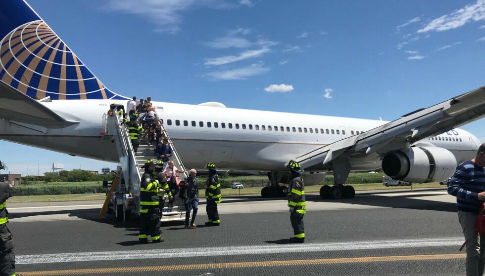 Passasjerer går av flyet fra United Airlines som skjenet av rullebanen etter at dekkene eksploderte under landing. Det ødelagte landingsutstyret skal ha havnet i gresset på Newark Liberty International Airport. Foto: Caroline Craddock / AP / NTB scanpix