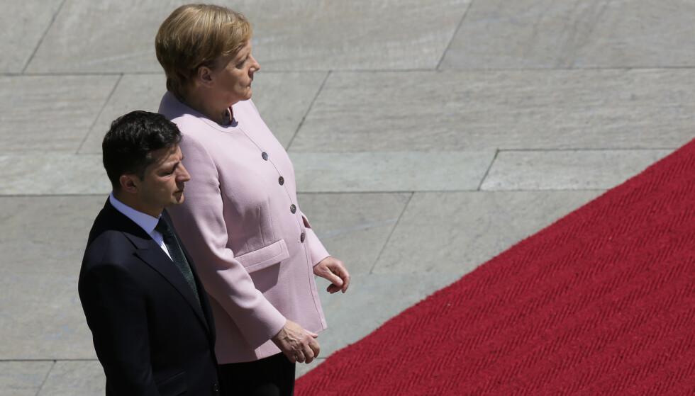 Tysklands statsminister Angela Merkel begynte å skjelve mens hun og Ukrainas president Volodymyr Zelenskyj hørte et militærorkester spille landenes nasjonalsanger. Foto: Markus Schreiber / AP / NTB scanpix