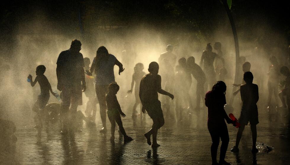 Folk kjøler seg ned i vannet i parken Madrid Río i Spanias hovedstad. Foto: AP / NTB scanpix