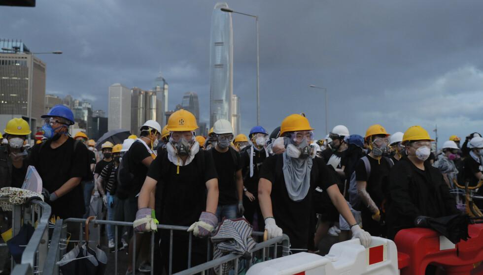 Demonstranter med hjelmer og gassmasker forsøker å sperre en vei som leder inn til området der det markeres at det er 22 år siden Hongkong ble overført til Kina. Foto: Kin Cheung / AP / NTB scanpix