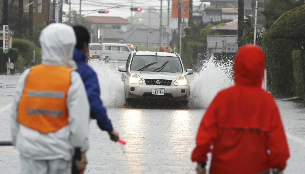 En bil kjører på en oversvømt vei i byen Miyakonojo onsdag. Foto: Kyodo News / AP / NTB scanpix