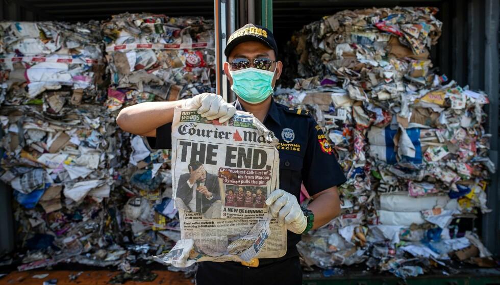En indonesisk grensevakt holder frem en avis fra en container fra Australia fylt med søppel. Foto: NTB scanpix / AFP