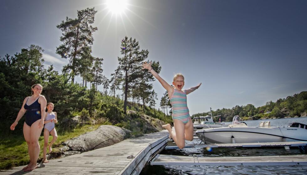 Hopp i sjøen mens sola skinner på dagtid. Det er varmt vær i det meste av landet, men kan komme en del ettermiddagsbyger. Her hopper Ingrid Gjerstad (9) ut i sjøen mens mamma Kristin og venninnen Frøydis Holst Hamran (9) følger med fra land på Grosplassen i Langåresund i Kragerø. Foto: Geir Olsen / NTB scanpix