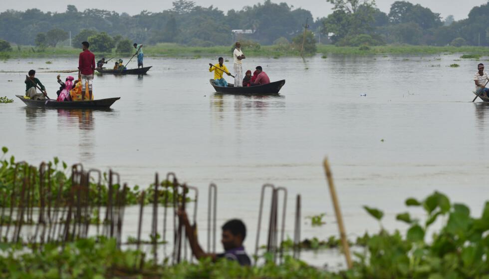 Indiske landsbybeboere i Assam-delstaten krysser flomvannet i båter fredag. Foto: AP Photo / NTB scanpix