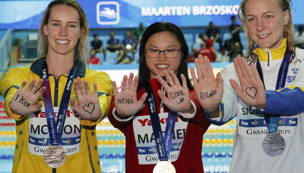 Australske Emma McKeon (til venstre) canadiske Margaret MacNeil (i midten) og svenske Sarah Sjöström (til høyre) sendte denne beskjeden til sin konkurrent. Foto: Lee Jin-man / AP / NTB scanpix