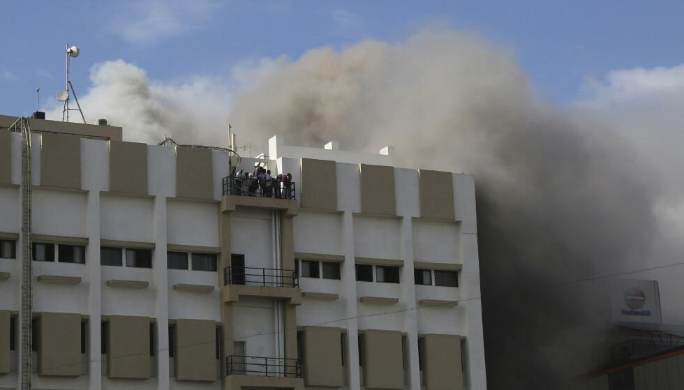 Folk ventet på å bli reddet ned fra den brennende bygningen i Mumbai. Foto: Rafiq Maqbool / AP / NTB scanpix