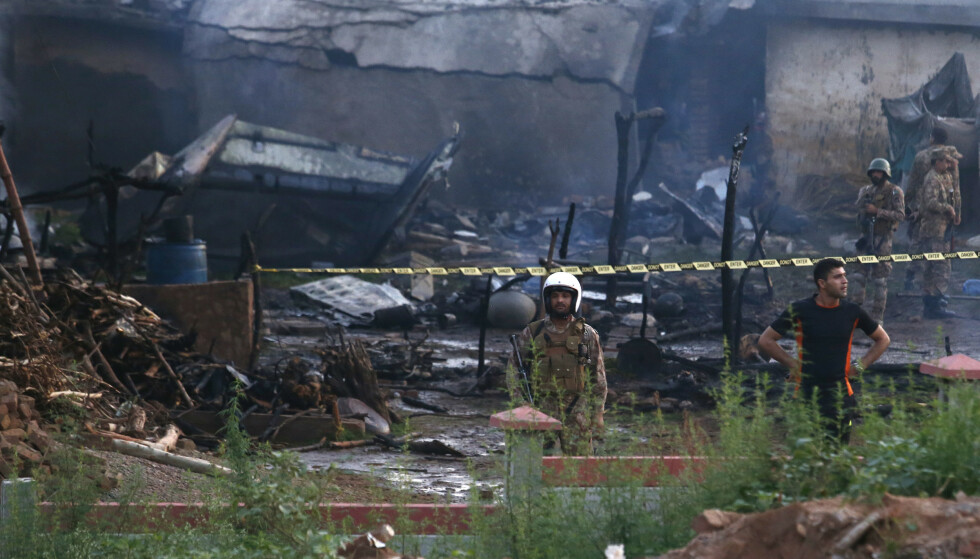 Nødetatene på stedet hvor et militærfly styrtet like før daggry tirsdag i en landsby utenfor Rawalpindi. Foto: AP / NTB scanpix