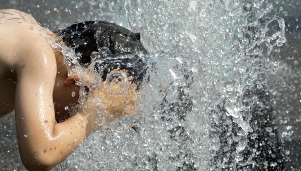 En gutt avkjølte hodet i en fontene i Antwerpen i Belgia torsdag i forrige uke, da den europeiske hetebølgen var på sitt mest intense. I Belgia og fire andre europeiske land ble det satt nye nasjonale varmerekorder denne dagen. Foto: Virginia Mayo / AP / NTB scanpix