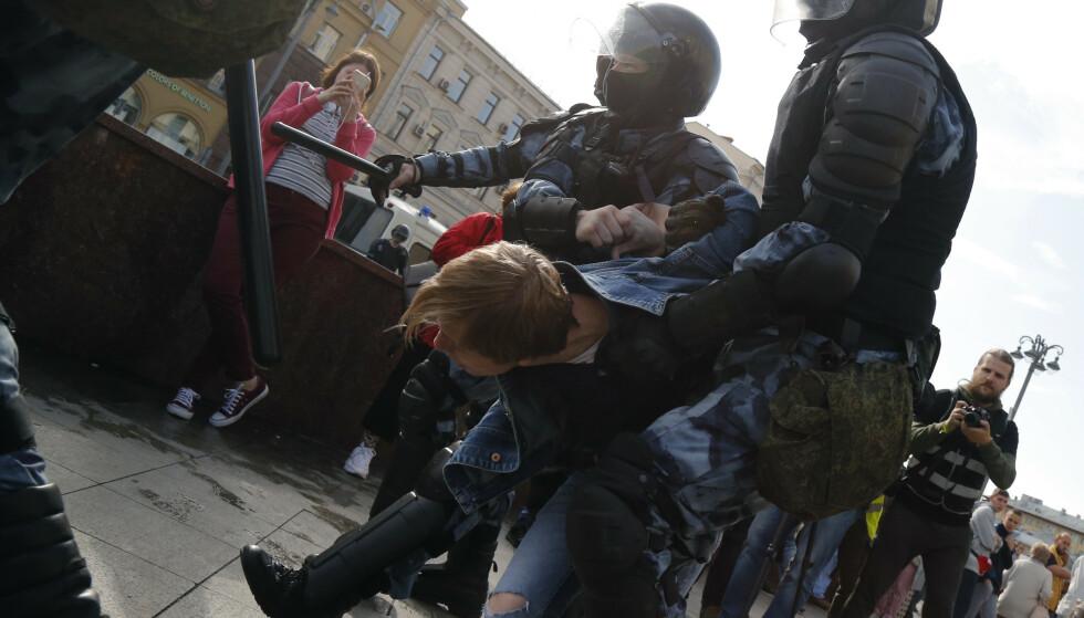 Politifolk pågriper en demonstrant i Moskva lørdag. Over 300 skal ha blitt pågrepet, opplyser uavhengige observatører. Foto: Alexander Zemlianichenko / AP / NTB scanpix