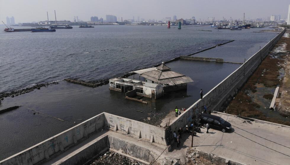 Myndighetene har bygd en gigantisk vegg for å hindre sjøen i å flomme inn over land i Jakarta. Rundt 40 prosent av storbyen ligger nå under havnivå. Foto: Achmad Ibrahim / AP / NTB scanpix.