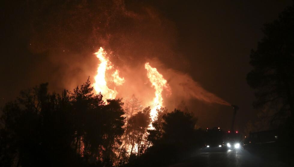 Brannmannskapene prøvde å stanse flammene i landsbyen Makrimalli med vann, med flere hundre brannfolk i sving tirsdag og natten gjennom. Fire landsbyer og et kloster på øya er evakuert. Foto: Yorgos Karahalis / Intime News / AP / NTB scanpix