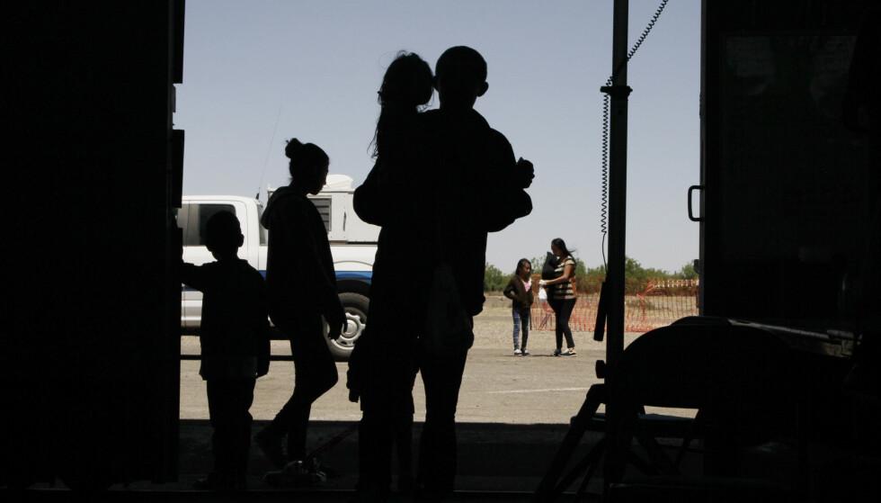 Latinamerikanske migranter venter utenfor et senter i New Mexico i USA på dette arkivbildet fra mai. Nå har Trump-administrasjonen bestemt seg for å oppheve begrensningen på hvor lenge migrantbarn kan sitte innesperret. Foto: AP / NTB scanpix