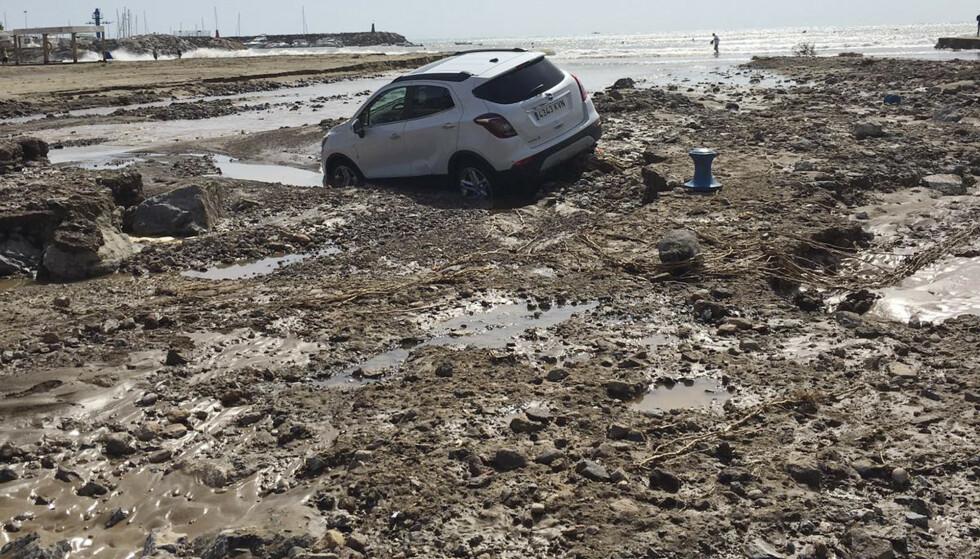 En bil ligger i gjørma i San Jose i Almeria i Spania etter at ekstremregn førte til store oversvømmelser. Seks mennesker mistet livet i uværet. Foto: Serge Carthwright / AP / NTB scanpix