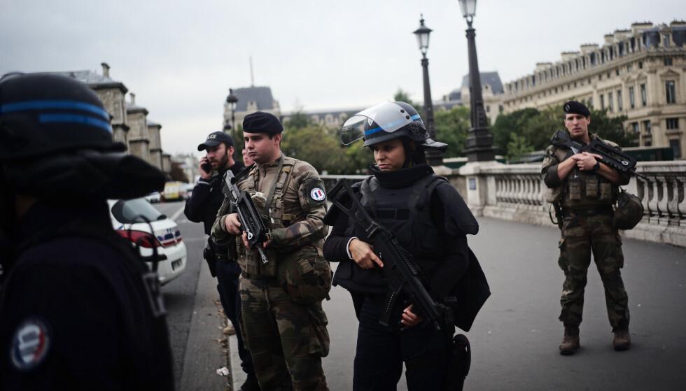 Bevæpnet politi og soldater vokter gaten utenfor hovedkvarteret i Paris. Foto: Kamil Zihnioglu / AP / NTB scanpix