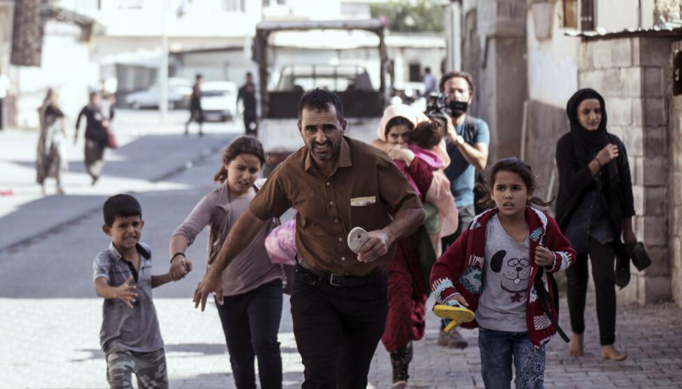 Folk i den tyrkiske grensebyen Akcakale løper for å søke ly for granatangrep fra syrisk side av grensen. Foto: Ismail Coskun / IHA via AP / NTB scanpix
