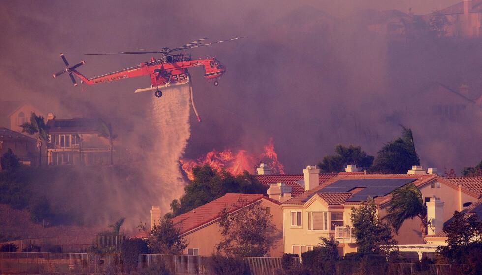 Et brannslokningshelikopter forsøker å slukke flammene som nærmer seg bolighus i Los Angeles fredag. Foto: AP / NTB scanpix