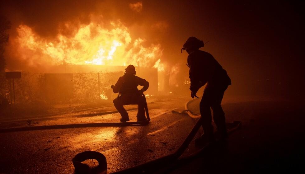 Brannfolk forsøker å redde en bolig fra den såkalte Getty-brannen som brøt ut før daggry mandag utenfor Los Angeles. Foto: Christian Monterrosa / AP / NTB scanpix
