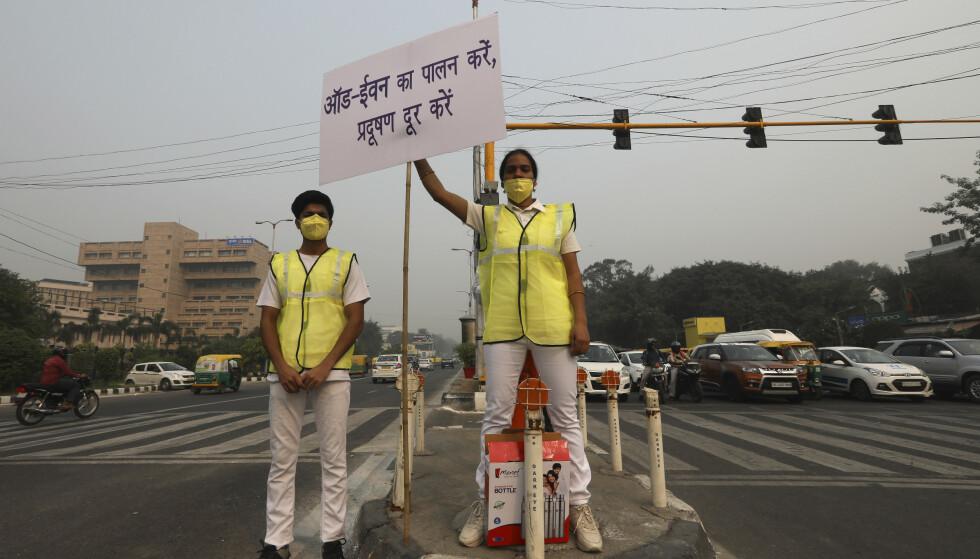 Frivillige med beskyttelsesmasker står ved et veikryss i New Delhi og oppfordrer bilistene til å overholde det nye påbudet med par- og oddetallskjøring. Myndighetene håper det skal få ned den alvorlige luftforurensningen i Indias hovedstad. Foto: Manish Swarup/ Ap/NTB scanpix
