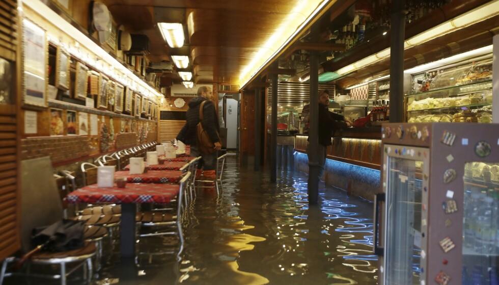 En oversvømmet kafé i Venezia. Byen ble rammet av store oversvømmelser tirsdag på grunn av mye nedbør og sterk vind. Foto: AP / NTB scanpix