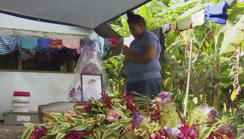 En kvinne ber ved et bilde av sitt avdøde barn i Apia i Samoa etter at en meslingepidemi har ført til at omkring 50 barn har mistet livet i landet. Foto: AP / NTB scanpix
