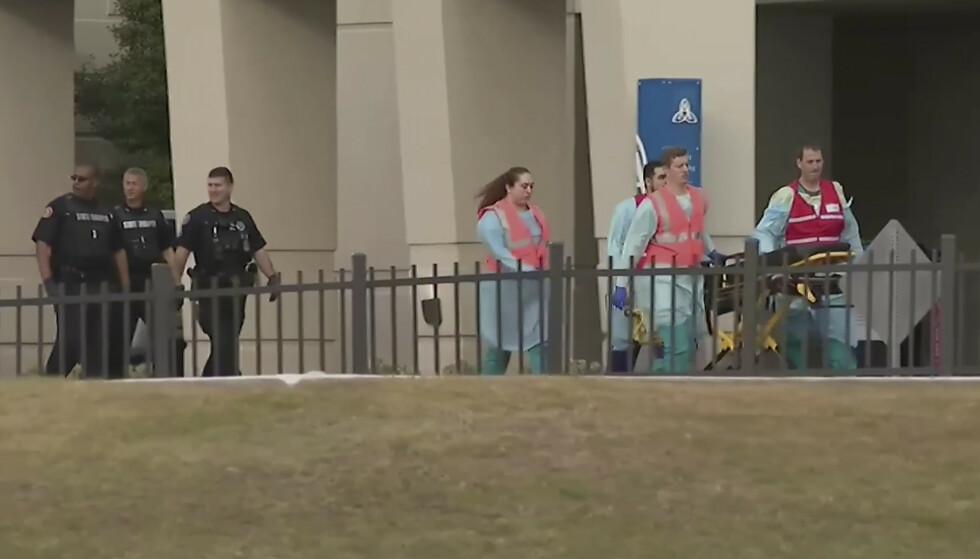 Ambulansepersonell i aksjon utenfor marinens flybase i Pensacola i Florida fredag. Tre personer ble skutt og drept av en mann fra det saudiarabiske flyvåpenet som var på basen for å gjennomgå opplæring. Foto: WEAR-TV via AP / NTB scanpix