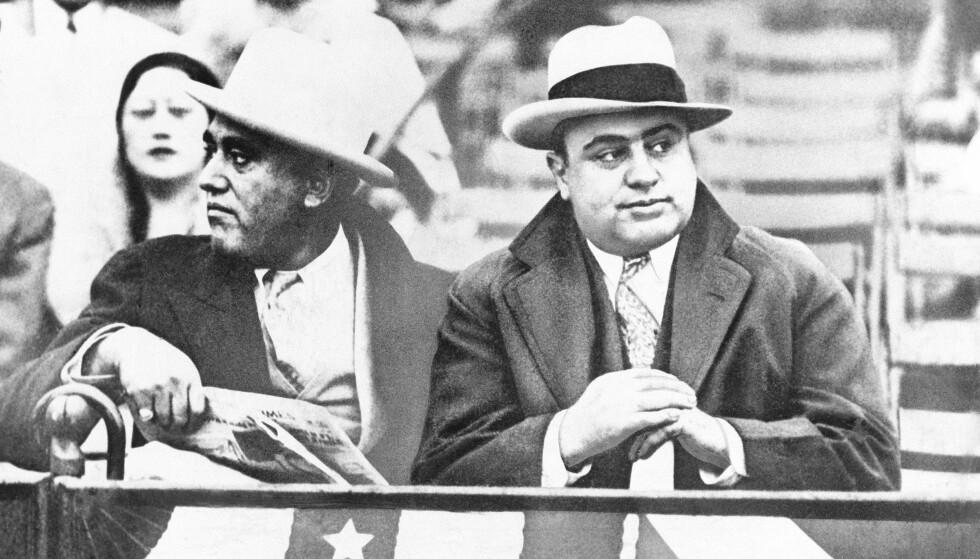 Gangsteren Al Capone (t.h.) på en amerikansk fotballkamp i Chicago. Al Capone tjente millioner av dollar på ulovlig spritsalg. Arkivfoto: AP / NTB scanpix