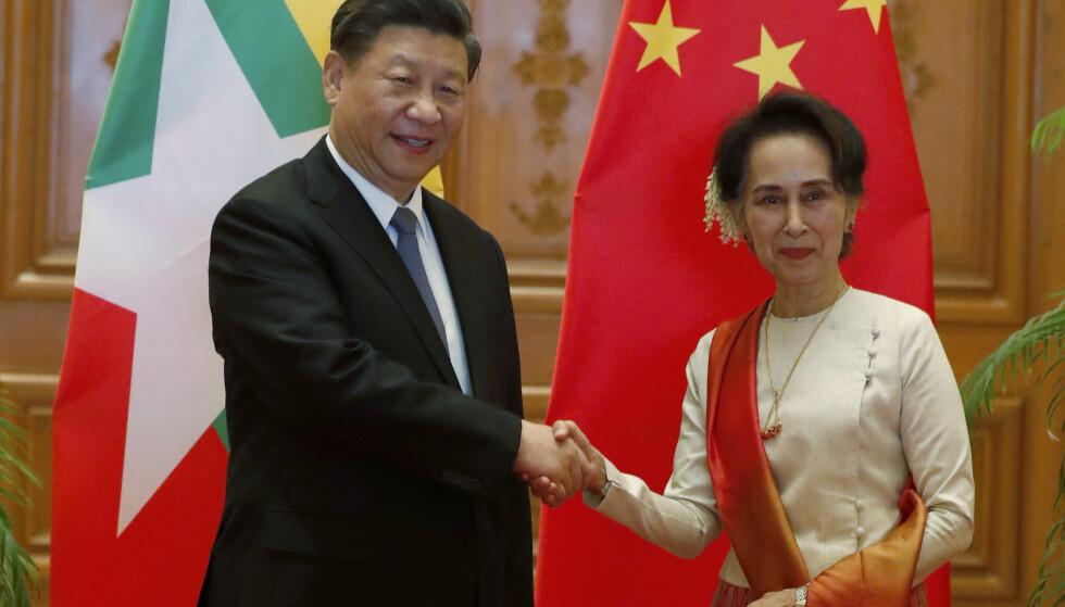 Myanmars sivile leder Aung San Suu Kyi og den kinesiske presidenten Xi Jinping tar hverandre i hånden under toppmøtet. Foto: AP / NTB scanpix