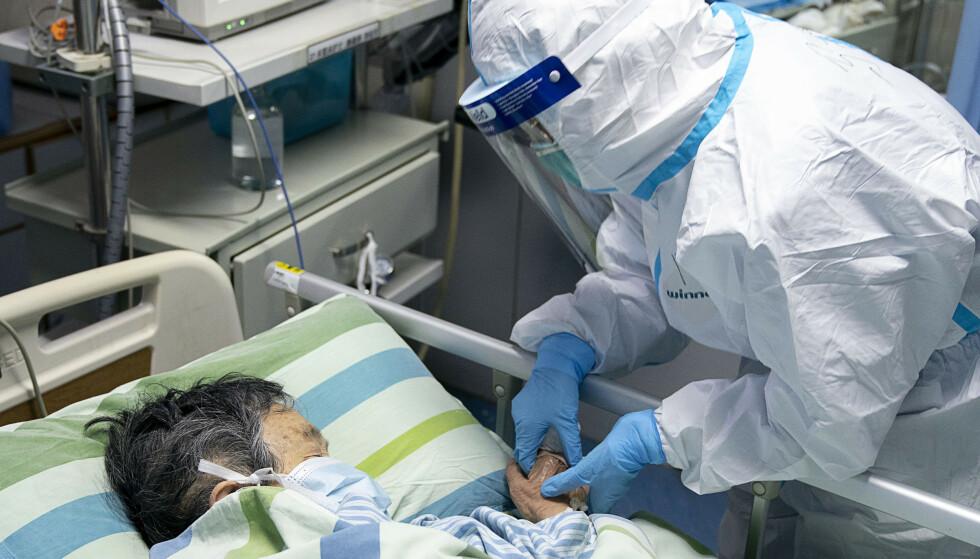 En helsearbeider ser til en innlagt på et sykehus i Wuhan, byen hvor virusutbruddet har rammet hardest. Foto: Xinhua / AP / NTB scanpix.