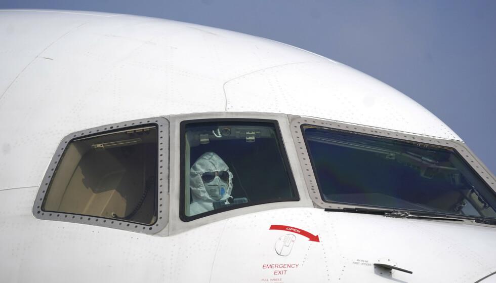 En pilot i et fly på flyplassen i Wuhan i Kina tirsdag. Flere land har startet evakuering av sine borgere vekk fra byen som betegnes som episenteret for utbruddet av den dødelige varianten av coronaviruset som er påvist. Foto: Cheng Min/Xinhua/ AP/ NTB scanp