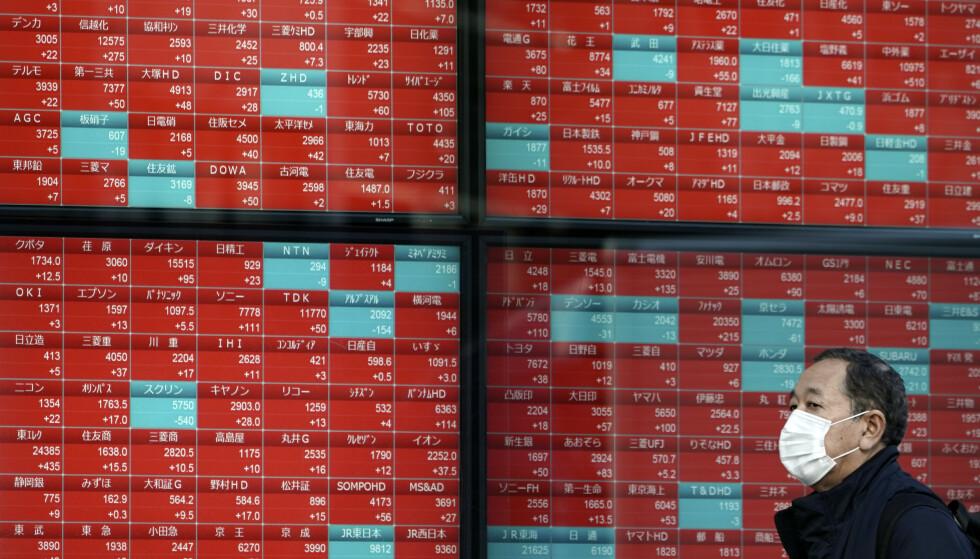 En mann passerer oversikten over Nikkei-indeksen i Tokyo fredag. Shanghai-indeksen i Kina falt 8,7 prosent ved åpning mandag som følge av økende frykt for at Wuhan-viruset vil dempe global vekst i økonomien. Illustrasjonsfoto: Eugene Hoshiko / AP / NTB scanpix
