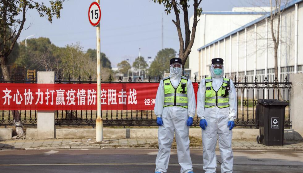 WHO sier utbruddet av Wuhan-viruset ikke foreløpig er å regne som en pandemi. Her politifolk i beskyttelsesutstyr som står vakt utenfor et hotell i Wuhan der virussmittede holdes isolert. Foto: Chinatopix via AP / NTB scanpix.